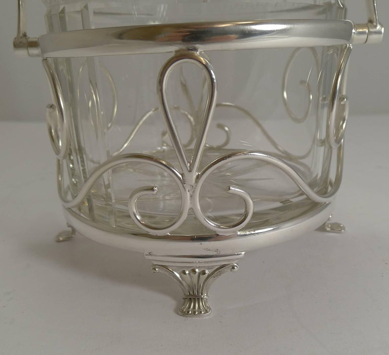 A wonderfully decorative biscuit box, the frame made from EPNS (Electro-plated nickel silver) and fully marked by the Birmingham silversmith, Arnold E Williams, it stands on four pretty feet.  The box itself is made from a hefty piece of English