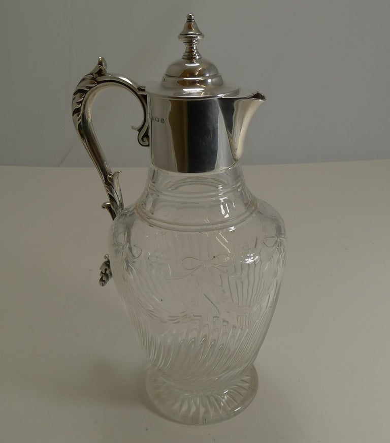 A fabulous antique crystal claret jug with the underside of the foot with a star cut. The body of the jug has long diagonal channel cuts and above this, a very pretty ribbon and bow continuous garland.  The fittings are all solid English sterling