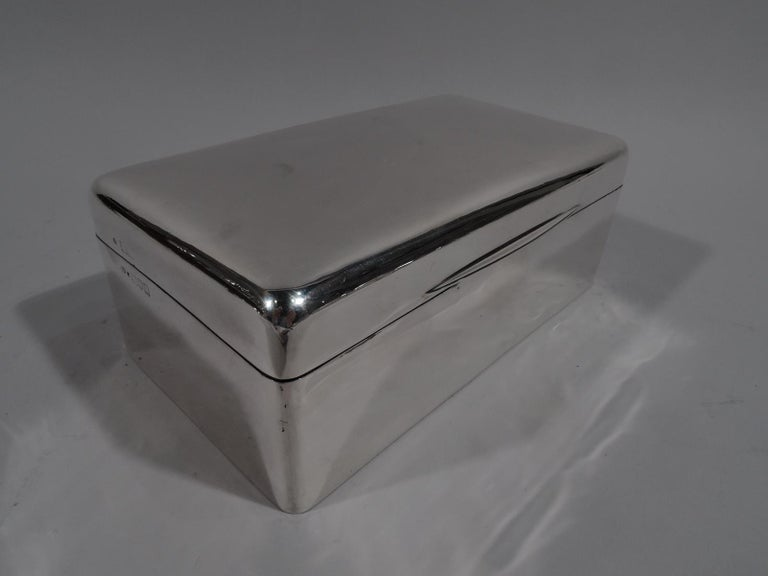 Edwardian modern sterling silver box. Made by Frederick Haberling in London in 1905. Rectangular with straight sides and curved corners. Cover hinged and gently curved with tapering tab. Box and cover interior cedar lined and partitioned. Underside