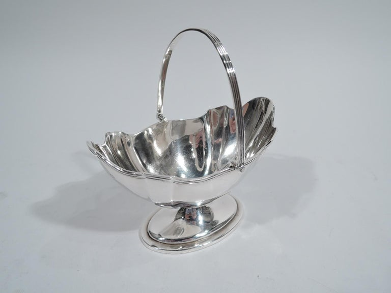 Edwardian neoclassical sterling silver sugar basket. Made by Thomas Bradbury & Sons in London in 1903. Boat-form and paneled bowl with molded curvilinear rim and stepped oval foot. Reeded C-scroll swing handle. Fully marked.   Dimensions: H (with