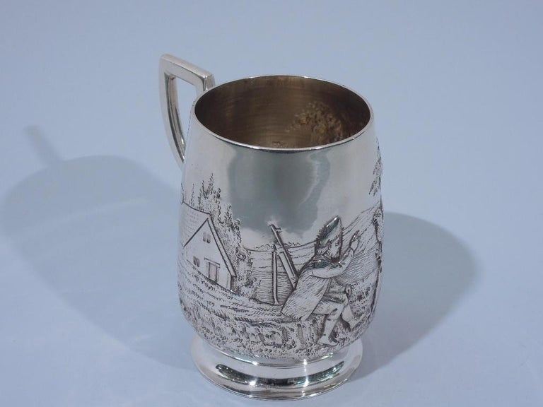 Edwardian sterling silver baby cup. Made by Francis Higgins in London in 1907. Upward tapering sides, raised and spread foot, and scroll bracket handle. Chased scene with countryman reaching out to a perched bird with cottage a picket fence in