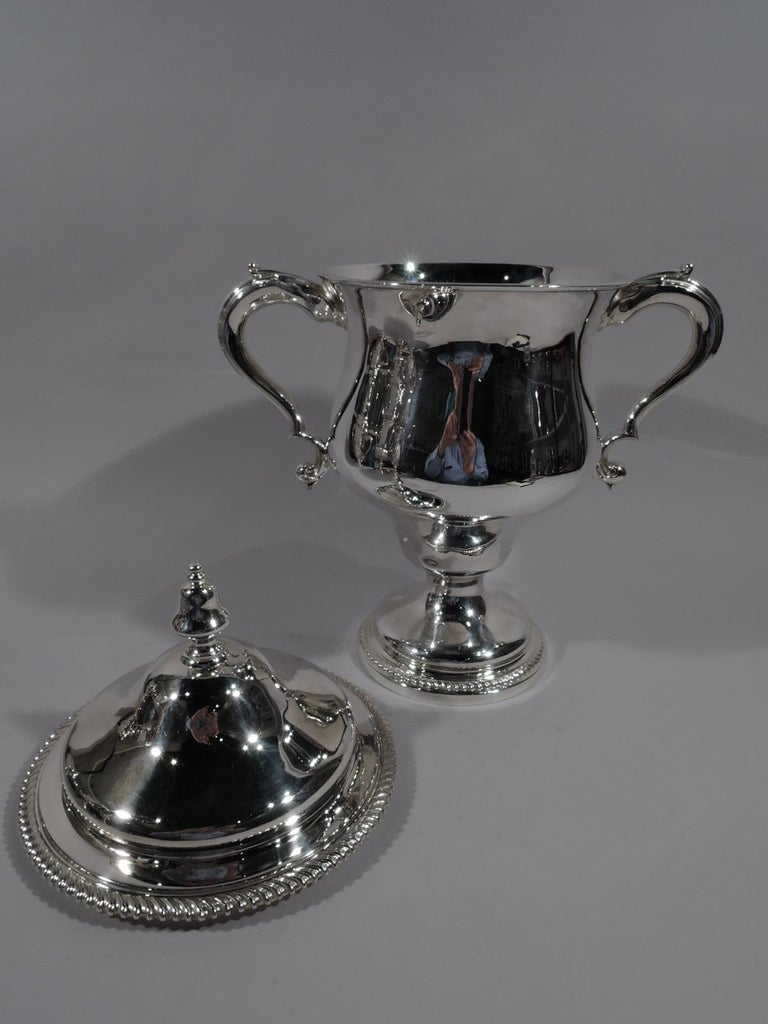 Edwardian sterling silver Classical covered urn. Made by Martin, Hall & Co. Ltd in Sheffield in 1904. Deep and wide-bodied baluster with leaf-capped double-scroll side handles and domed foot. Cover domed with acorn finial. Gadrooned rims.
