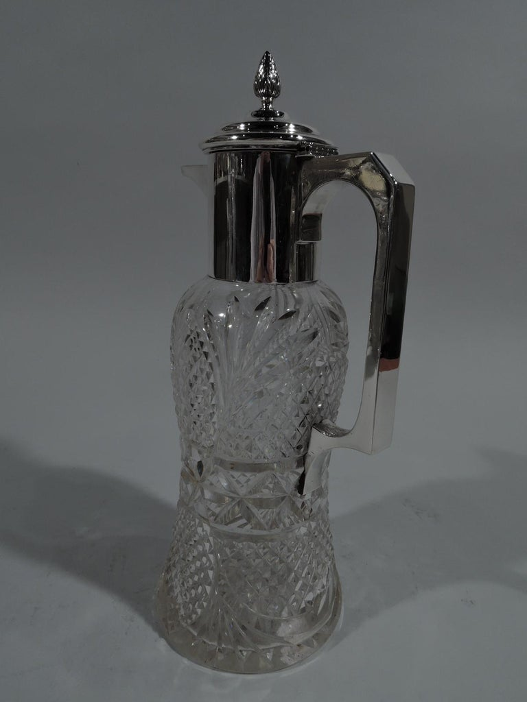 Edwardian cut-glass and sterling silver decanter. Made in Birmingham in 1910. Waisted cylinder with all-over ferns, facets, and stars. Sterling silver bracket handle, neck collar, and stepped and hinged cover with bud finial and spout. Fully marked
