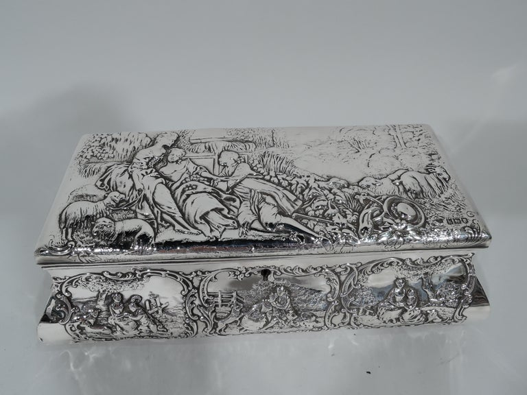 Edwardian sterling silver jewelry box. Made by William Comyns in London in 1905. Long and bombe with hinged cover. Chaste courting scenes in scrolled frames: Georgian ladies and gentlemen kneel, touch, and play. On cover the man pursues a woman who