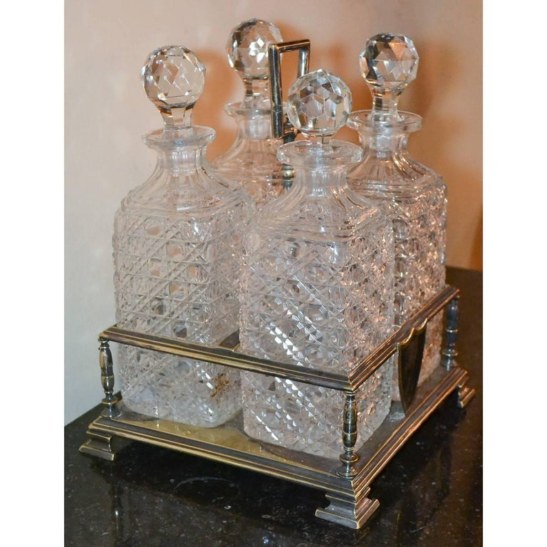19th century English tantalus/decanter four bottle set with stand, circa 1890. Silver plate over brass Measures: 12 height x 9 inches wide x 9 inches deep.