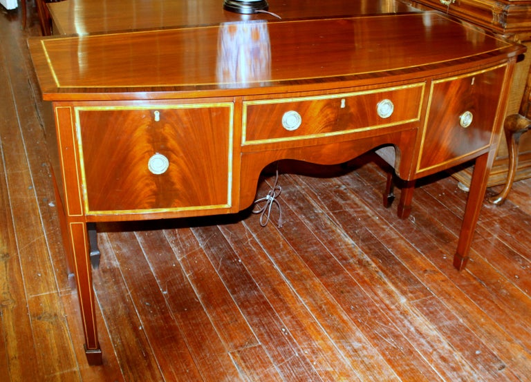 Superb quality antique English George III inlaid flame mahogany Hepplewhite style bowfront sideboard with gorgeous book-matched crotch or flame mahogany drawer fronts.  Please note rosewood and satinwood cross-banding (inlay) and right sided