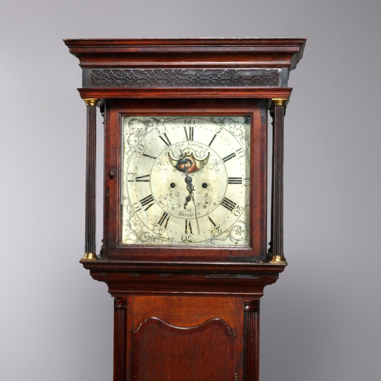 An antique George III longcase clock offers English oak construction with moulded cornice hood with reeded pilasters having bronze capitals and bases; porcelain foon phase face with Roman numerals and signed Sam Ashton, Bredbury, 18th