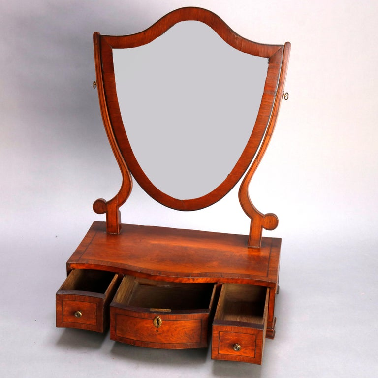 An antique English Georgian dresser shaving mirror offers flame mahogany construction with shield form mirror surmounting crossbanded base with three drawers and raised on bracket feet, circa 1810  ***DELIVERY NOTICE – Due to COVID-19 we are