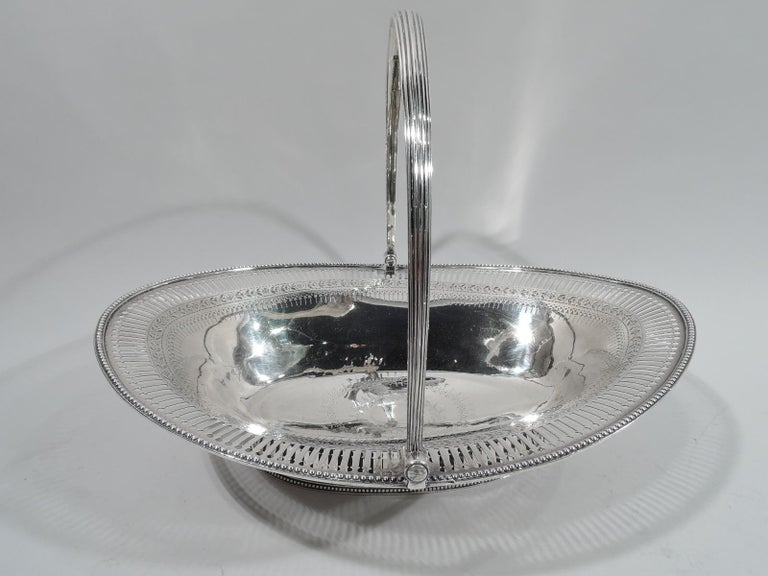 English Georgian neoclassical sterling silver basket, ca 1790. Ovoid body on same foot with reeded c-scroll swing handle. Engraved wavy-shaped frame (vacant) and ornamental borders. Linear and circular piercing and beading. Partially worn marks