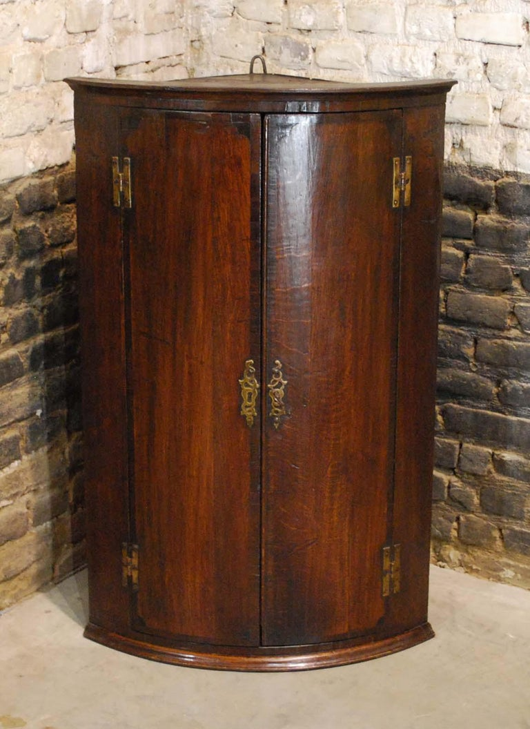 This elegant antique hanging corner cabinet was made in England circa 1860. 