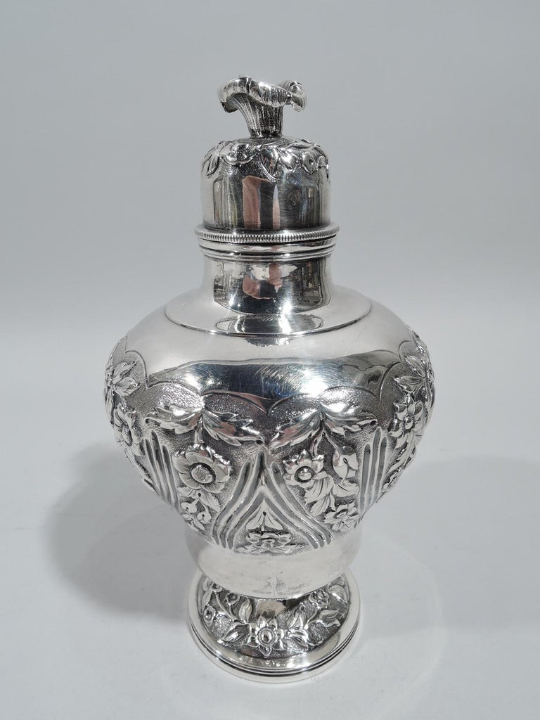 George IV sterling silver tea caddy. Made by Richard Pierce & George Burrows in London in 1829. Baluster with raised foot. Short neck and domed cover with flower finial. Chased floral garlands on stippled ground. On body garlands alternate with