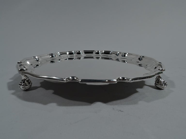 George V sterling silver salver. Made by Ellis & Co. in London in 1927. Round with sharp and molded curvilinear piecrust rim. Three claw-and-ball supports. Fully marked including retailer's stamp for JE Caldwell in Philadelphia. Weight: 5.5 troy