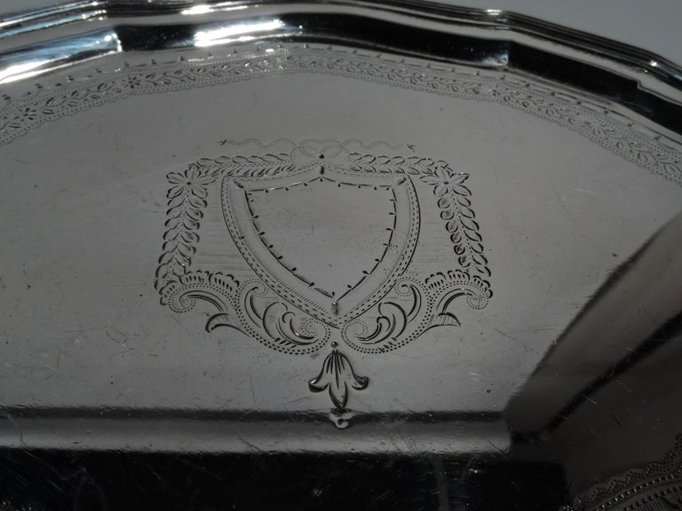 George V sterling silver salver. Made by Ellis Jacob Greenberg in Birmingham in 1923. Curvilinear cartouche with molded rim on 4 triangular supports. Engraved armorial (vacant) and ornamental border. Hallmarked. Weight: 6 troy ounces.