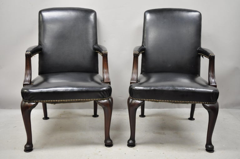 Antique English Georgian style dark green leather library office chairs - a pair. Item features nailhead trim, solid wood frame, upholstered armrests, dark green leather upholstery, very nice antique item, quality American craftsmanship. Currently
