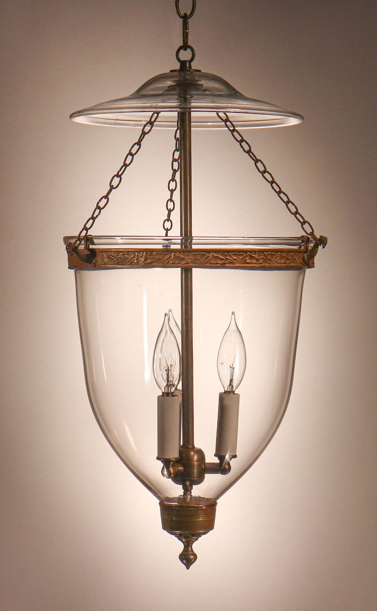 A beautiful, classic English bell jar lantern with clear hand blown glass. This circa 1850 lantern features an original embossed band and teardrop finial/candleholder base. It has been newly electrified with a three-bulb candelabra cluster. The
