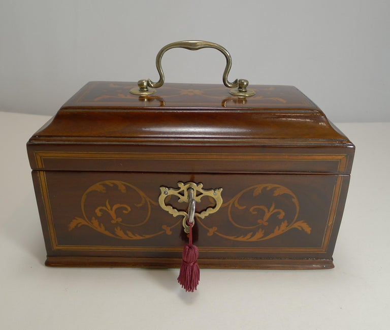 A very handsome George III tea caddy, made from Mahogany and beautifully inlaid with panels and highly decorative foliate marquetry to the front and top. The top has a handsome cast brass handle with a complimentary cast brass escutcheon which