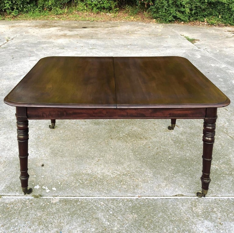 Antique English mahogany dining table with leaf features tailored lines and the richness of the natural beauty of the exotic imported mahogany to create the perfect dining surface. Sides slide out to create space for a single large leaf, as depicted