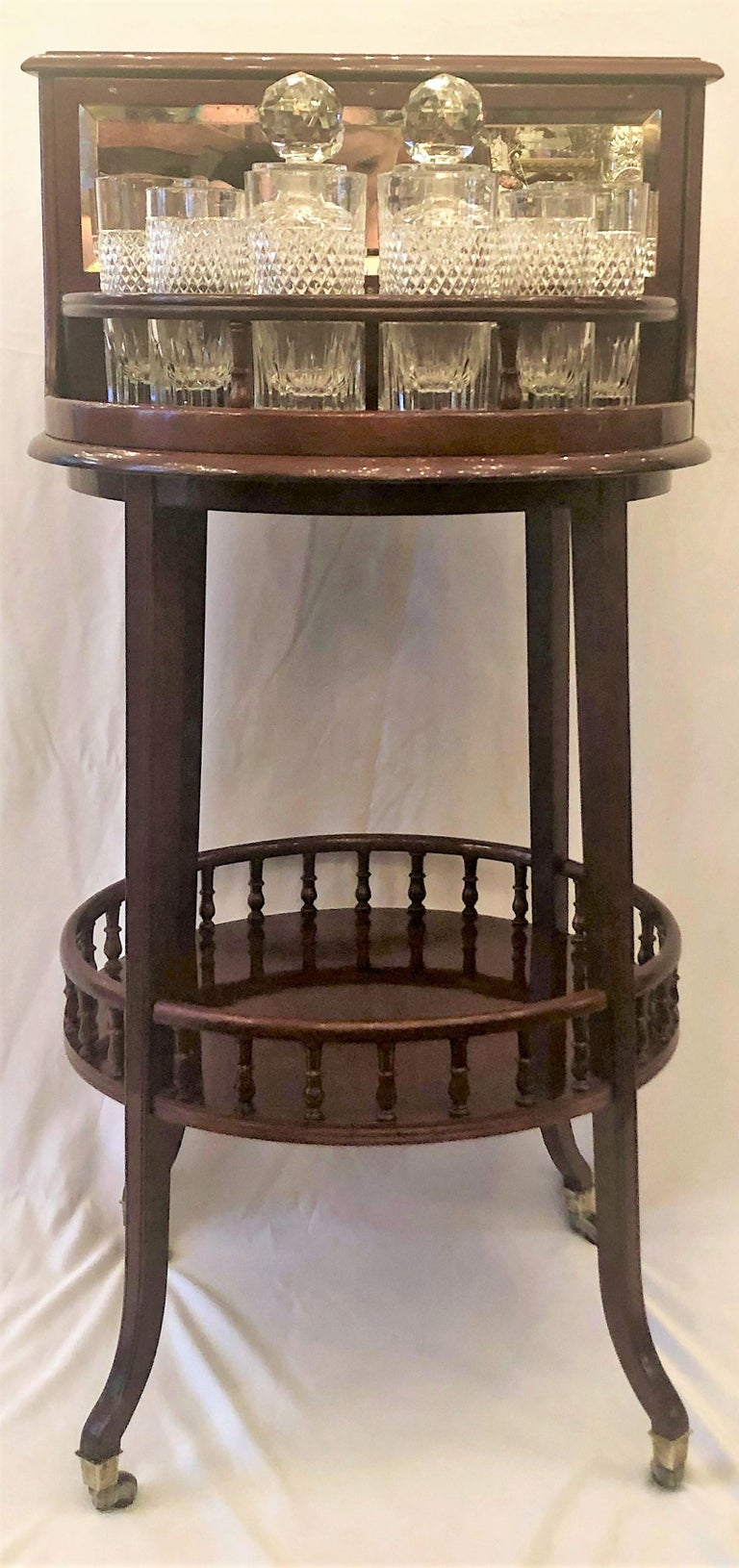 Antique English mahogany revolving hidden bar with cut crystal barware, made by