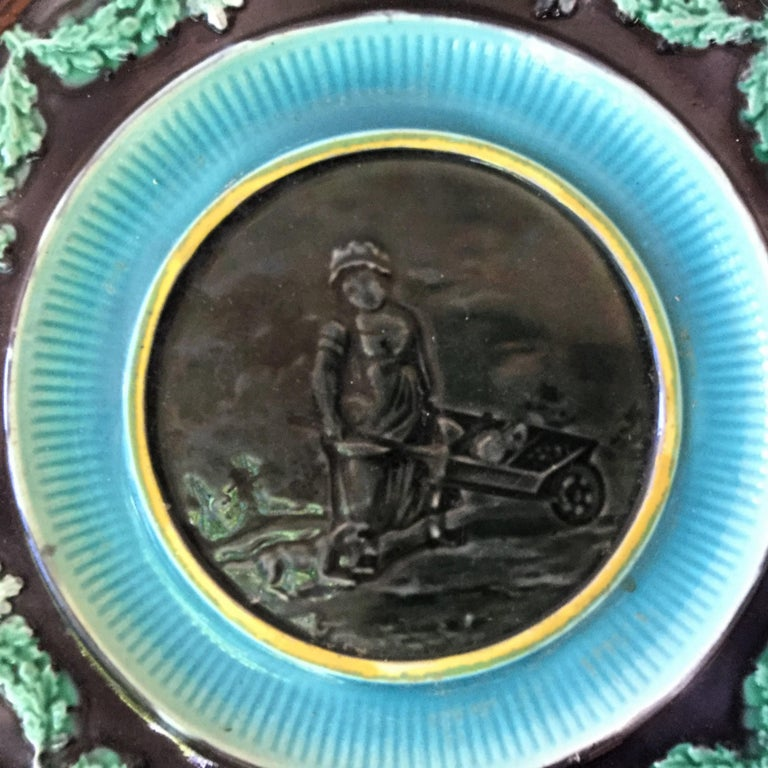 19th century English Majolica plate featuring a woman with a dog pushing a wheelbarrow bordered with a garland of oak leaves. No maker's mark.