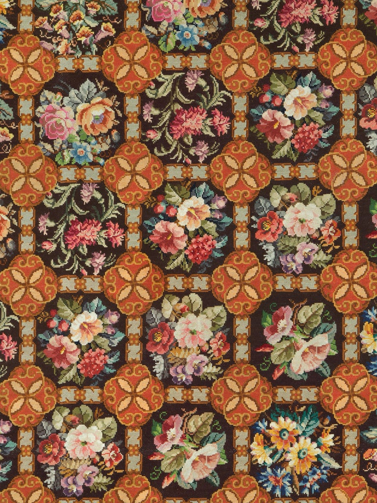 An antique English needlepoint carpet from the early 20th century.  Measures: 9' 3