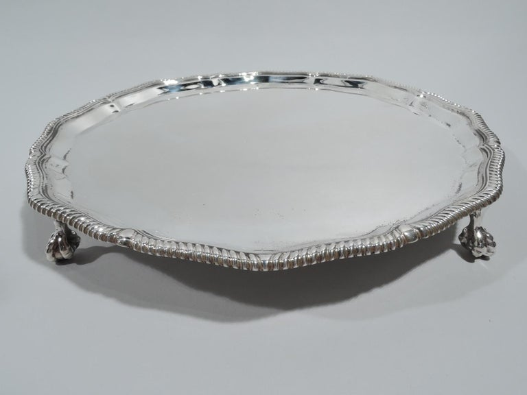 George V sterling silver salver. Made by Thomas Bradbury & Sons in Sheffield in 1921. Round shaped with gently scrolled and gadrooned rim and tapering sides. Four claw-and-ball feet. Traditional Neoclassicism. Fully marked. Weight: 19.5 troy ounces.