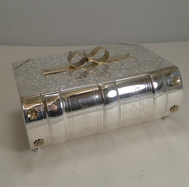 A rare biscuit box made in silver plate in the form of a book standing on four original little feet.  The