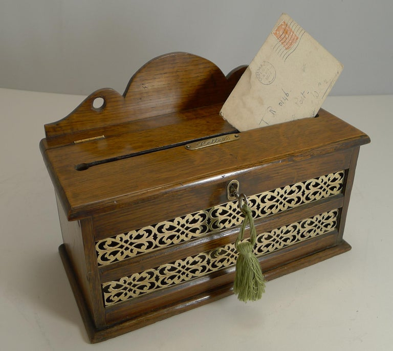 An unusual example, I have had many similar open at the top, but I have not had one of these as a closed box with a hinged lid.  Made from solid English oak, the front has a fretted brass panel allowing one to see if there were any letters
