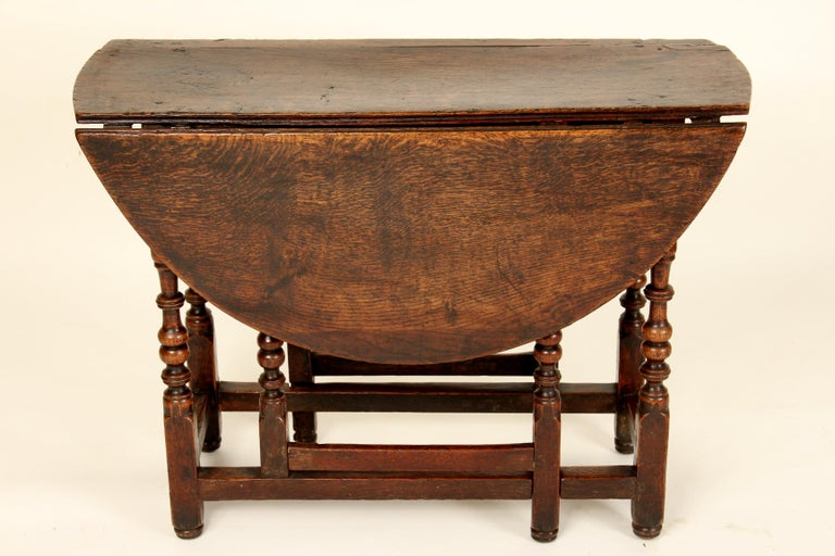 Antique English oak gate leg table, with nice old original patina, early 19th century. Dimensions when drop leafs are lowered, height 26.75