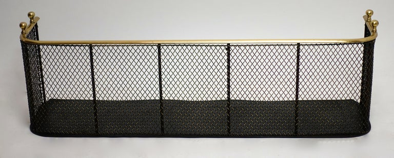 Handsome and useful English or American brass and black painted iron fire fender from the  early 19th century with four finials with an unusual heavy brass mesh screen in excellent antique condition.