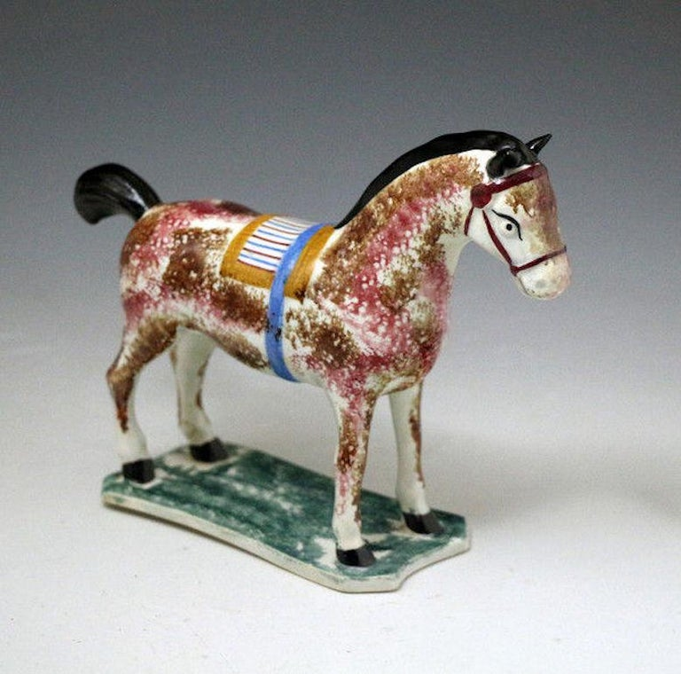 Pottery pearlware figure of a saddled horse standing on a thin green mottled coloured base.  The horse is sponge decorated in shades of maroon and brown a pleasing effect with the mustard , maroon and blue striped saddle with its blue strap. The