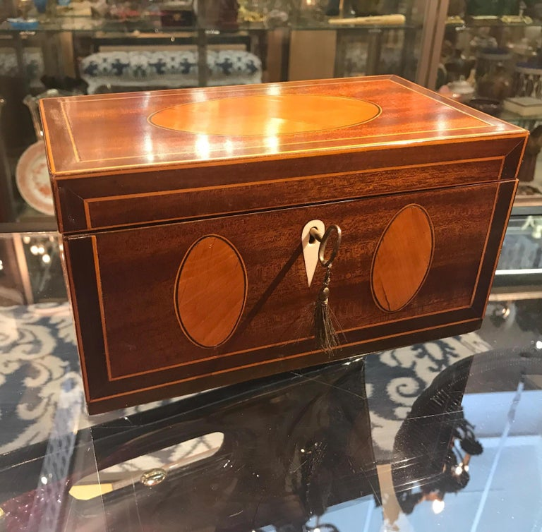 Pure elegance in mahogany and satinwood. This Regency style locking box with mahogany background with oval panels and hand inlaid stainwood with delicate ebony string inlay accent. The oval panes are a sign of a very skilled cabinetmaker. The paper
