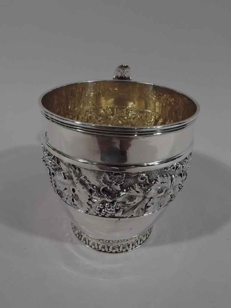 George IV sterling silver baby cup. Made by Rebecca Emes and Edward Barnard in London in 1833. Gently tapering sides with short foot and leaf-capped and reeded scroll bracket handle. Interior gilt washed. Wide repousse band with fruiting grapevine