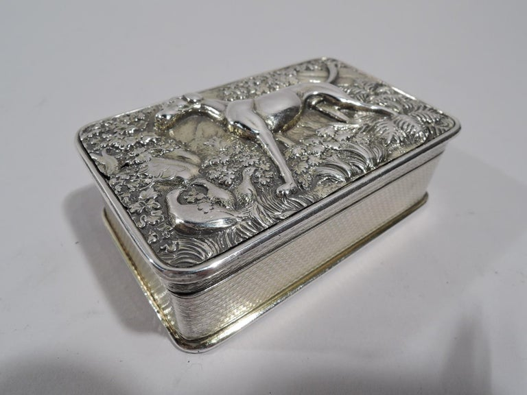 George III English sterling silver snuffbox, 1819. Rectangular with straight engine-turned sides and curved corners; underside also engine-turned. Cover hinged with low-relief hound standing alert amidst verdure, a few gamebirds tucked away in a
