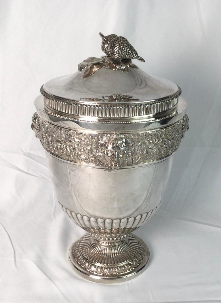A classic urn form ice bucket or wine cooler with a liner, England, circa 1900. The urn form with a finial on the lid of strawberries and leaves, the body at the top with cast decoration of grape leaves and masks of bacchanalia. The pedestal base