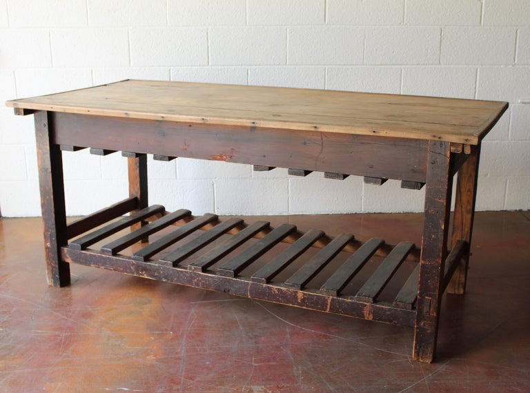 Interesting and very functional, this 19th century English silk cutting table would have been used in a dress maker's shop. The top is hinged to hold supplies. The bottom would have held fabric bolts. 21st century, it's great for a kitchen island,