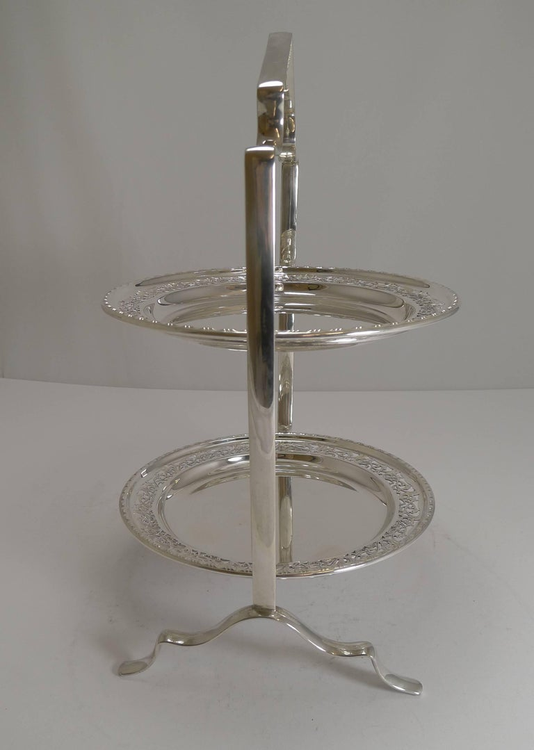 A most attractive Edwardian two-tier cake stand, made from English silver plate, the stand marked on the underside with the silversmith's initials (I believe for the Birmingham Guild of Handicrafts) and EPNS (Electro-Plated Nickel Silver).  The