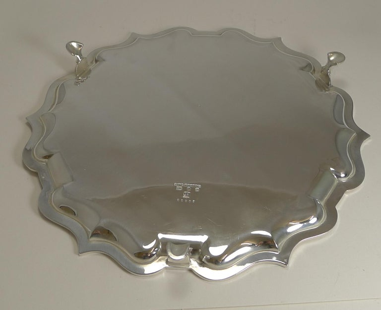 A beautiful and elegant antique English serving salver or drinks tray, beautifully shaped with a plain polished surface and standing on three legs.