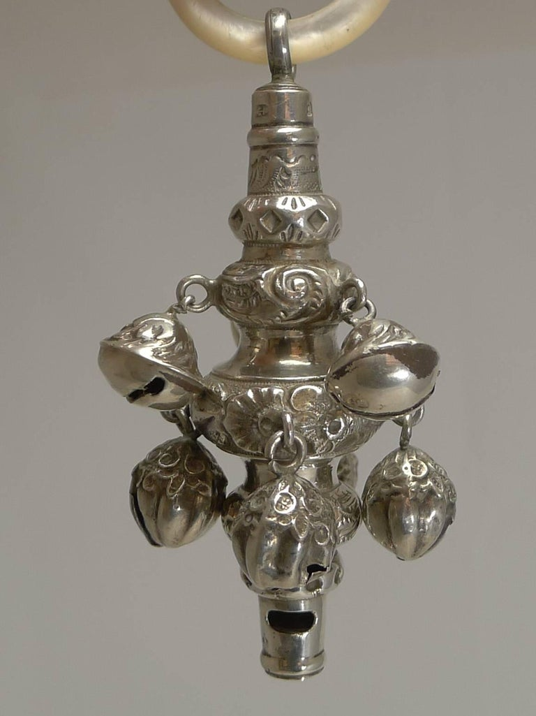 A beautiful English Victorian combined baby's rattle with an integral whistle, having eight bells and a mother-of-pearl teething ring.  All made from English sterling silver with repousse or embossed decoration and fully hallmarked for Birmingham