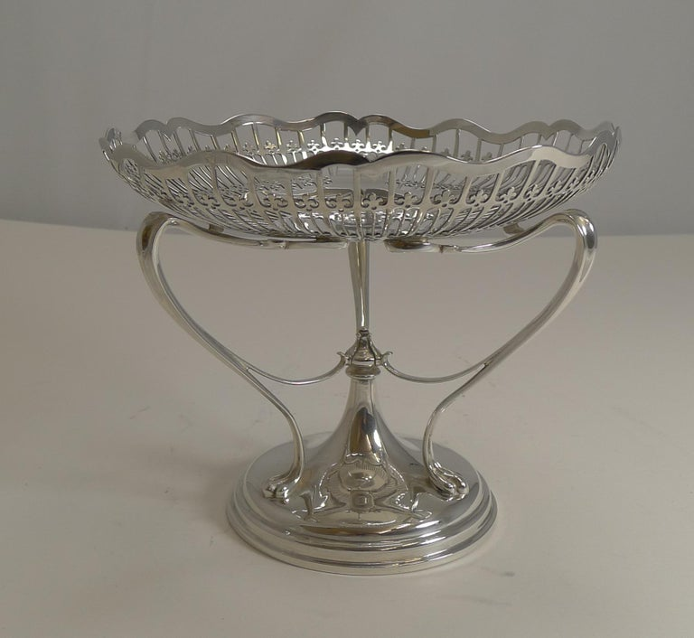 An exquisite top-quality Edwardian sterling silver comport with an Art Nouveau design seen in the organically shaped supports from the base to the bowl.  The bowl is beautifully pieced or reticulated with an elegantly shaped rim.  The silver is