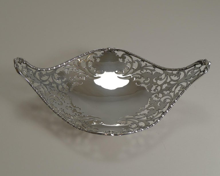 A really pretty Edwardian pieced or reticulated dish, beautifully shaped outlined with a beaded rim and a scroll decorated handle each end.  The dish has a full English hallmark for London 1908, Edwardian in era. The makers mark is also present