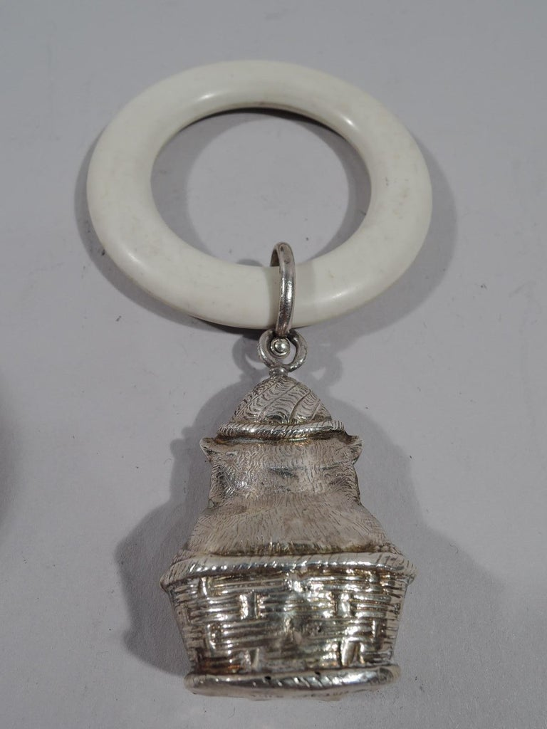 George V sterling silver baby rattle. Made by WH Collins & Co. in Birmingham in 1932. Flat and round ring with loose-mounted figural pendant: A cat in a basket with self-satisfied expression and fat paws. Nice jangly sound. Fully marked.