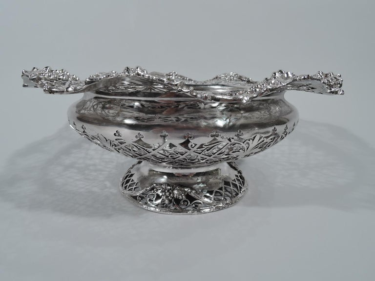 George V sterling silver bowl. Made by James Dixon & Sons in Sheffield in 1911. Bellied with domed foot. Solid multi-foil well and pierced trellis with stylized foliage. Wavy grapevine rim with applied bunches. Foot same. Perfect for the fruit and