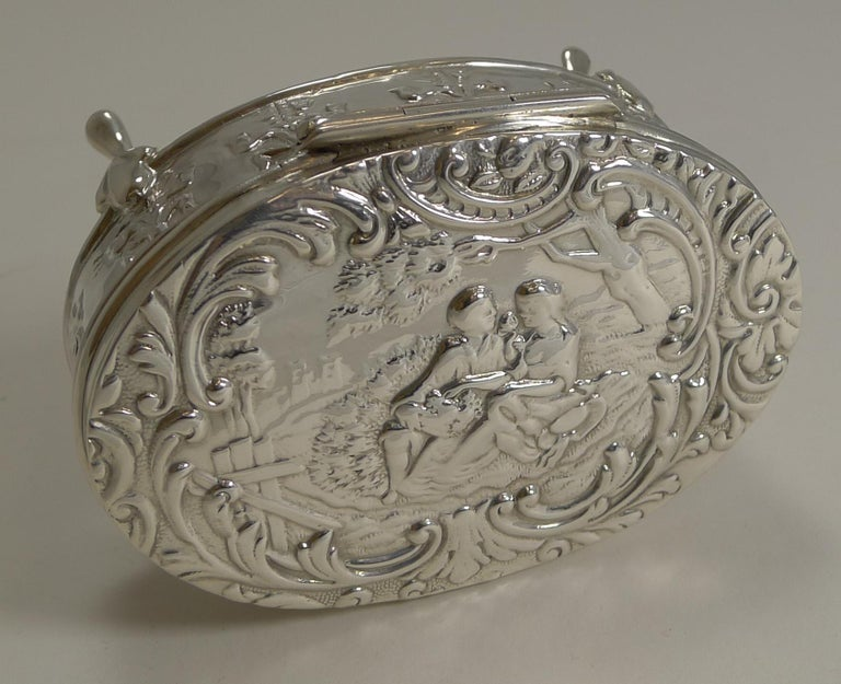 Pretty as a picture, this Edwardian oval sterling silver box stands on four elegant legs. The sides have an embossed or repousse decoration featuring a series of ribbon and bow motifs.  The lid is beautifully decorated with a romantic courting