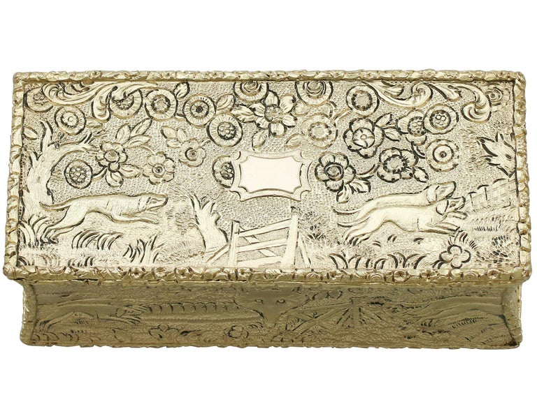 This exceptional antique George IV sterling silver gilt Snuff box has a rectangular waisted form.  The surface of this antique silver box is embellished with exceptional chased decoration depicting hunting hounds chasing a fox in an rural