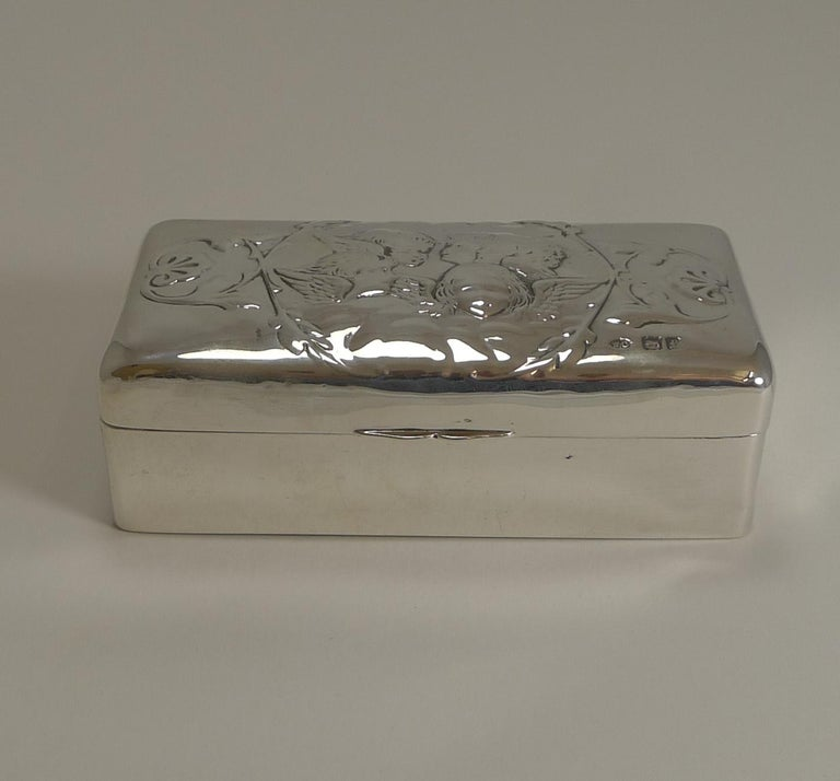 A wonderful solid box made from English sterling silver featuring the famous five winged Cherubs to the lid.  The hinged lid fits well and once opened, reveals a navy blue velvet and silk lining.  The box is fully hallmarked for London 1901