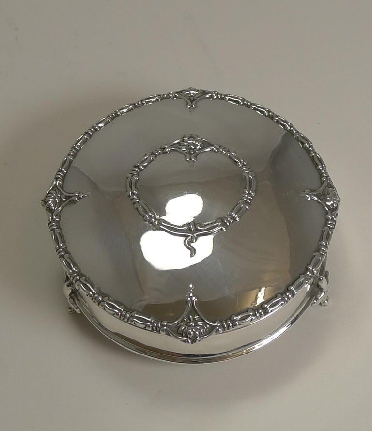 A beautifully decorated sterling silver jewellery or ring box standing on three elegant Fleur-de-Lys legs.