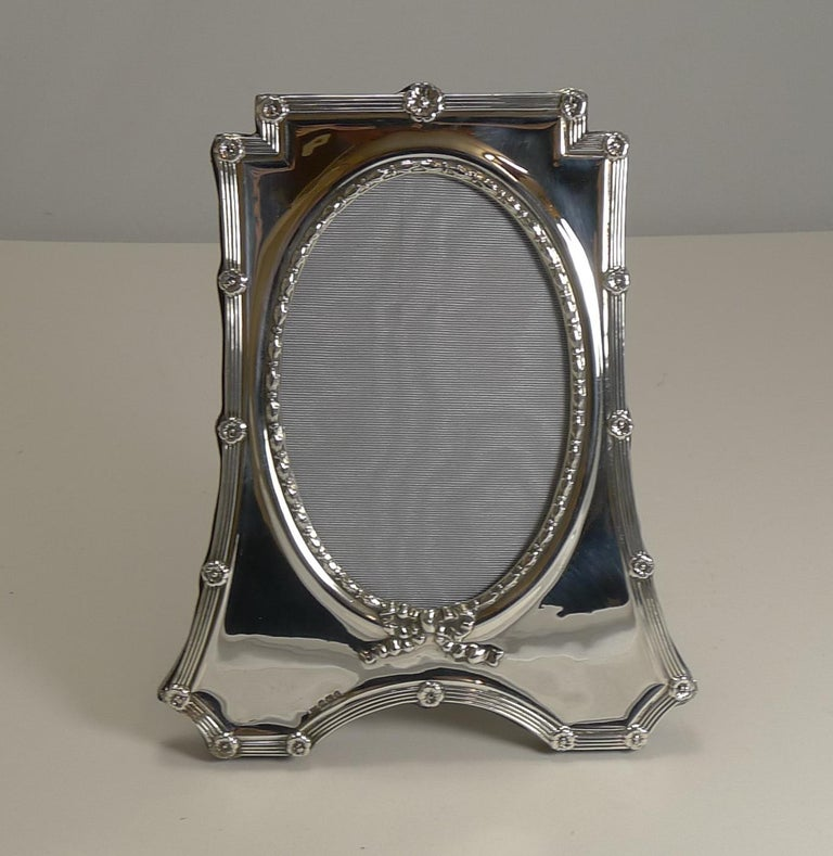 A beautifully shaped photograph frame made from English sterling silver with a solid oak backing with a folding easel stand.  The edge is decorated with a linear design punctuated with floral motifs; the oval aperture is surrounded with a raised