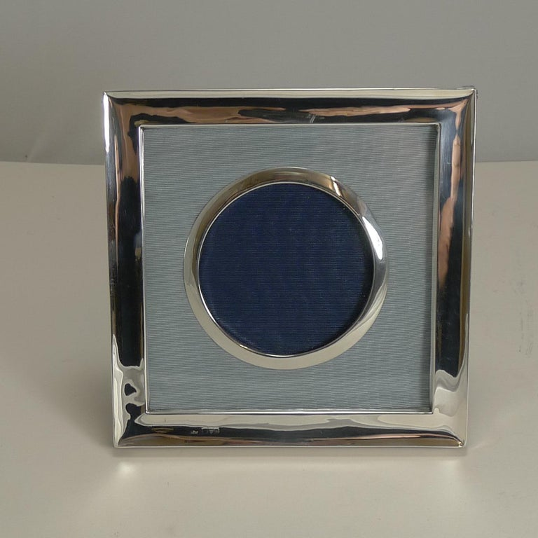 A very smart and elegant photograph frame, perfect for any decor, from traditional to modern.  The square frame retains it's original leather backing incorporating an easel back stand. The frame is lined in an ice blue silk taffeta then there is a