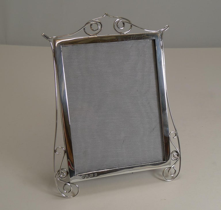 A wonderfully decorative and unusual Edwardian sterling silver frame by the top-notch silversmith, William Hutton and Sons.  The simple frame is decorated with sterling silver wire-work, creating two legs.  The back has a leather backing