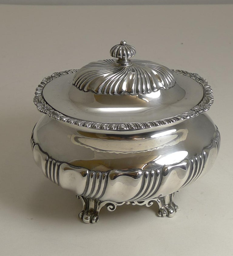 A stunning large and heavy tea caddy standing on pierced or reticulated cast base incorporating four feet, a fluted decoration to the body, hinged lid and finial; and an attractive cast border around the top of the caddy.  The silver is fully
